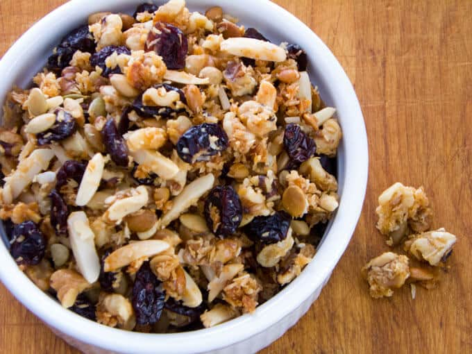Cranberry walnut granola in white bowl on cutting board