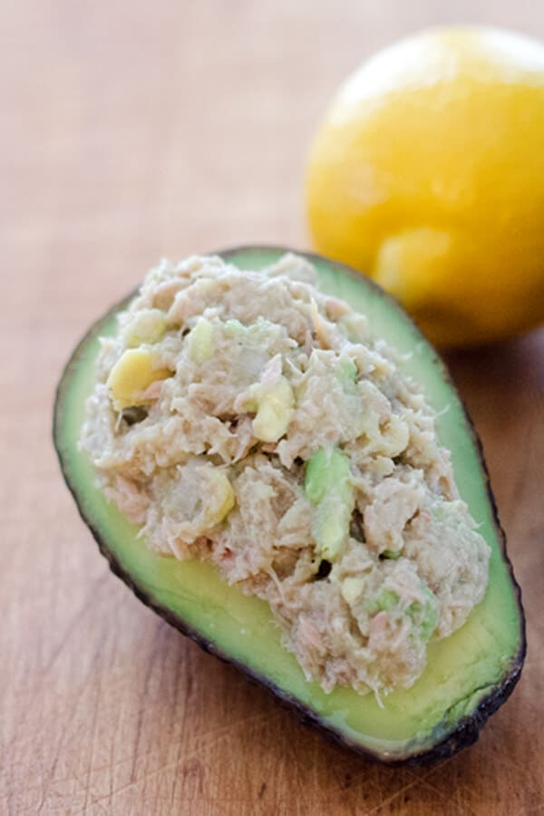 Avocado tuna salad stuffed in avocado with lemon on cutting board