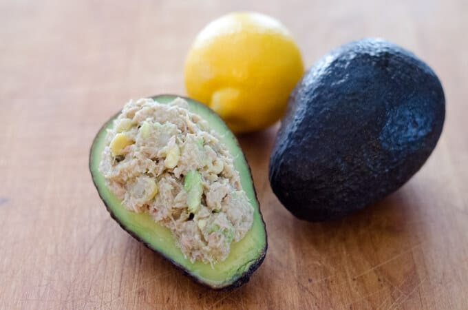 Tuna salad stuffed in avocado with lemon and Hass avocado on board
