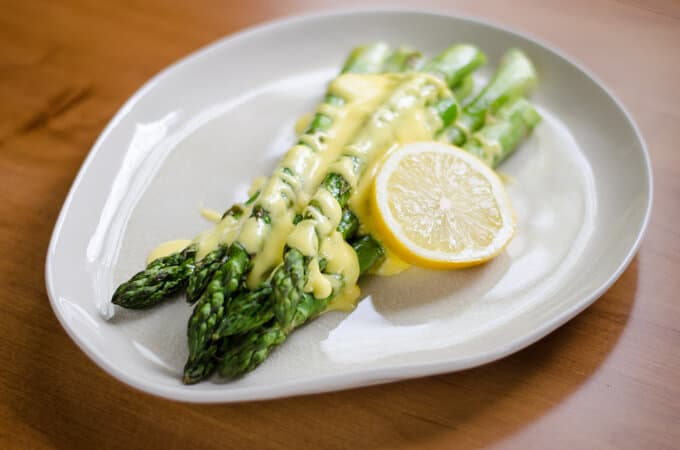 Asparagus with Hollandaise Sauce and lemon slice on plate