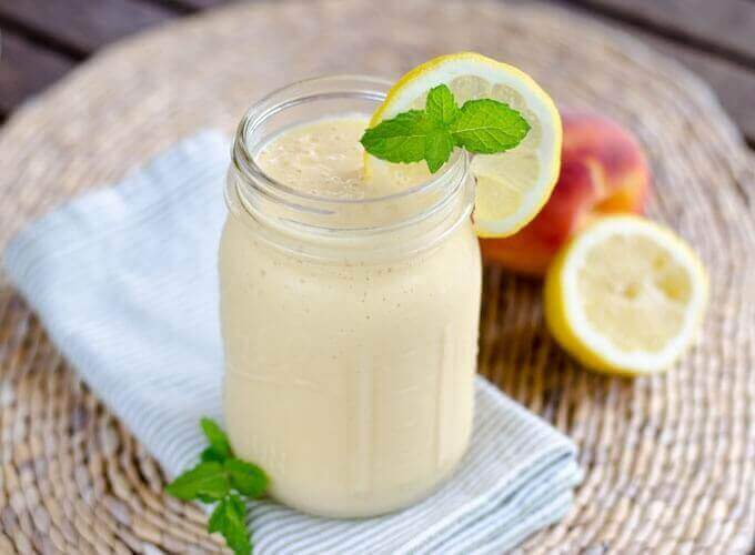 Peach coconut smoothie with lemon, peach and mint leaves.