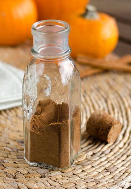 Homemade pumpkin pie spice in glass jar, pumpkins, cinnamon sticks