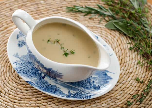 cauliflower gravy in gravy boat with herbs