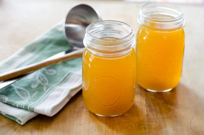 Crock Pot Chicken Stock in mason jars with ladle
