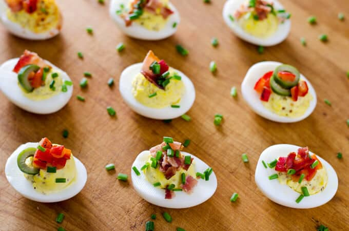 Deviled Eggs with Bacon and Chives on wood board