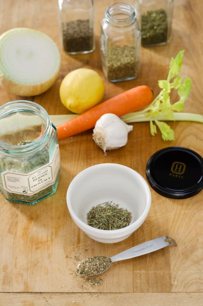 Homemade Herbes de Provence in bowl, spice jars, mirepoix ingredients