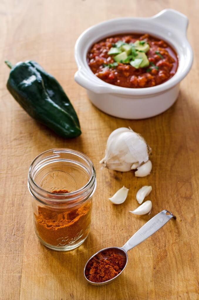 Homemade chili powder, garlic, poblano pepper and bowl of chili