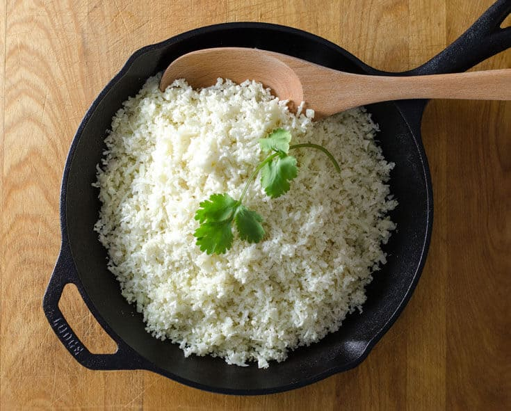 riced cauliflower in frying pan with cilantro