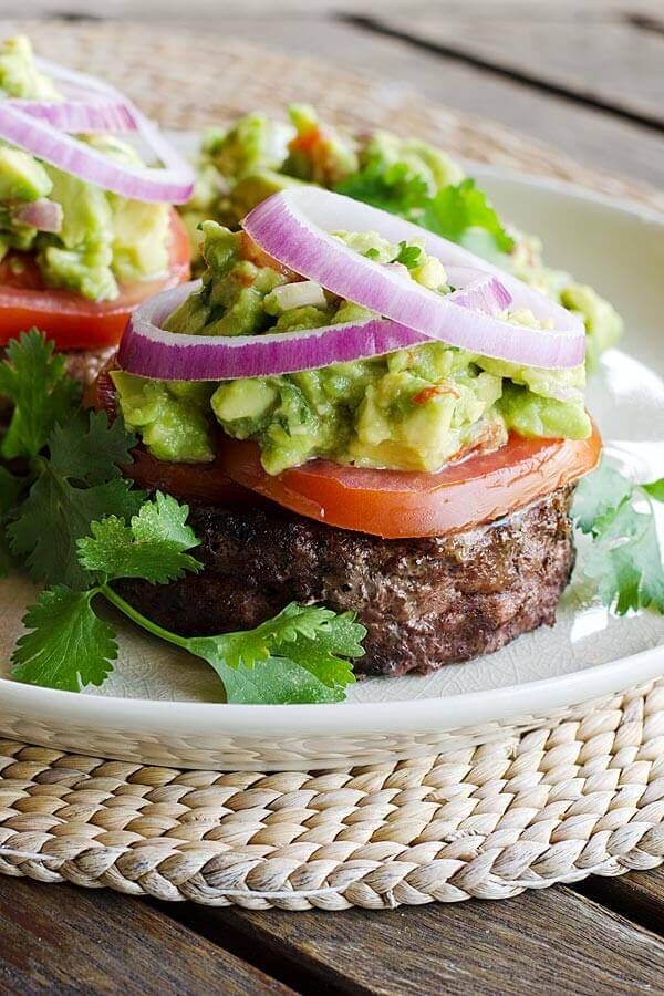 Grilled hamburger with guacamole, tomato, onion, and cilantro