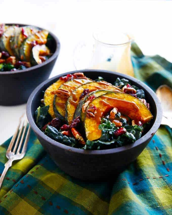 Kale salad recipe with roasted squash, pomegranate, and maple balsamic dressing from Lexi's Clean Kitchen. Winter Harvest Salad is paleo and vegan.