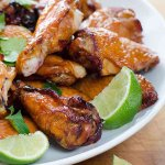 Crispy smoked chicken wings with lime wedges