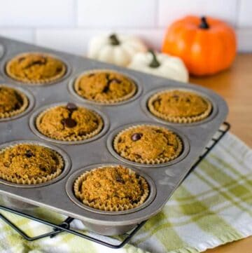 Pumpkin chocolate chip muffins on rack with pumpkins