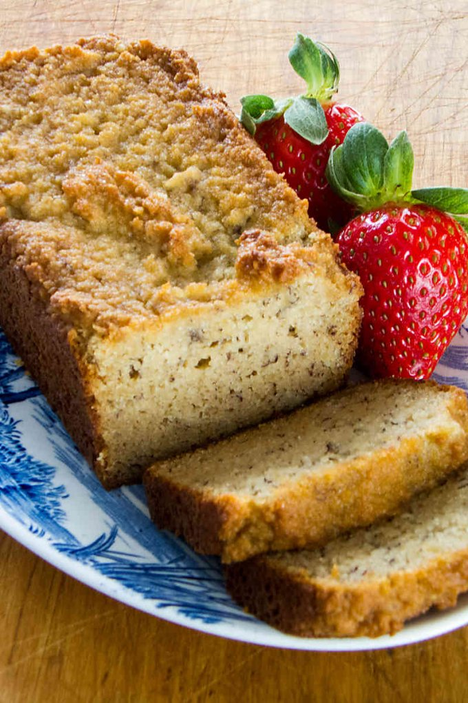 Paleo banana bread loaf with slices on plate with strawberries