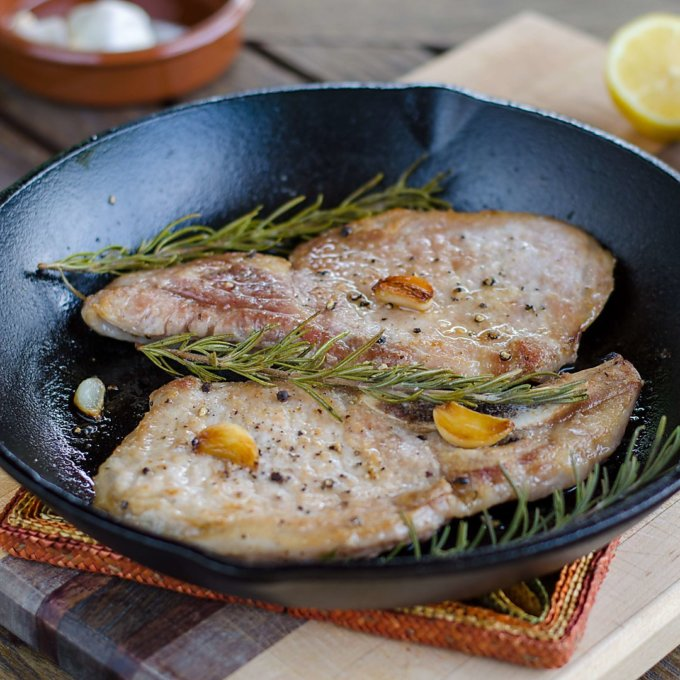 Pork chops with garlic and rosemary in cast iron pan