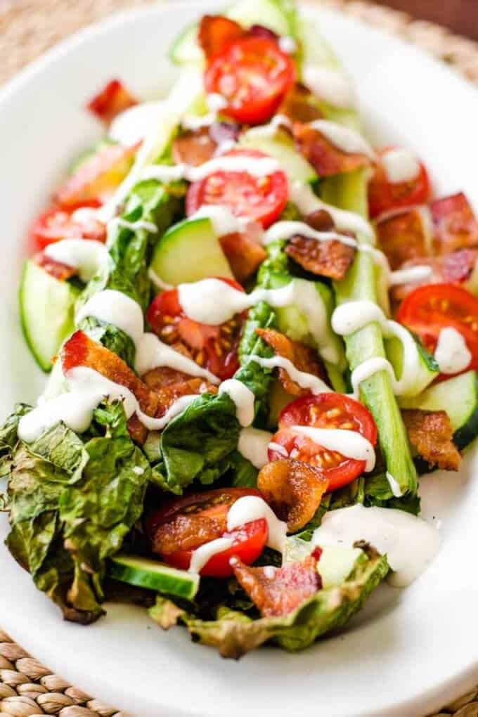 Grilled romaine salad with bacon, tomatoes, and ranch dressing