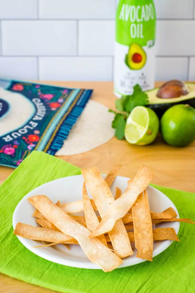 Baked tortilla strips on a plate, cassava flour tortillas, avocado oil, avocado, lime and cilantro.