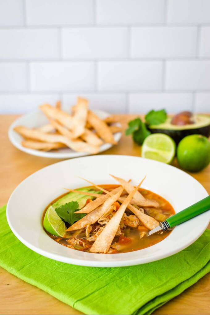 Bowl of chicken tortilla soup with lime, cilantro, avocado, and tortilla strips.