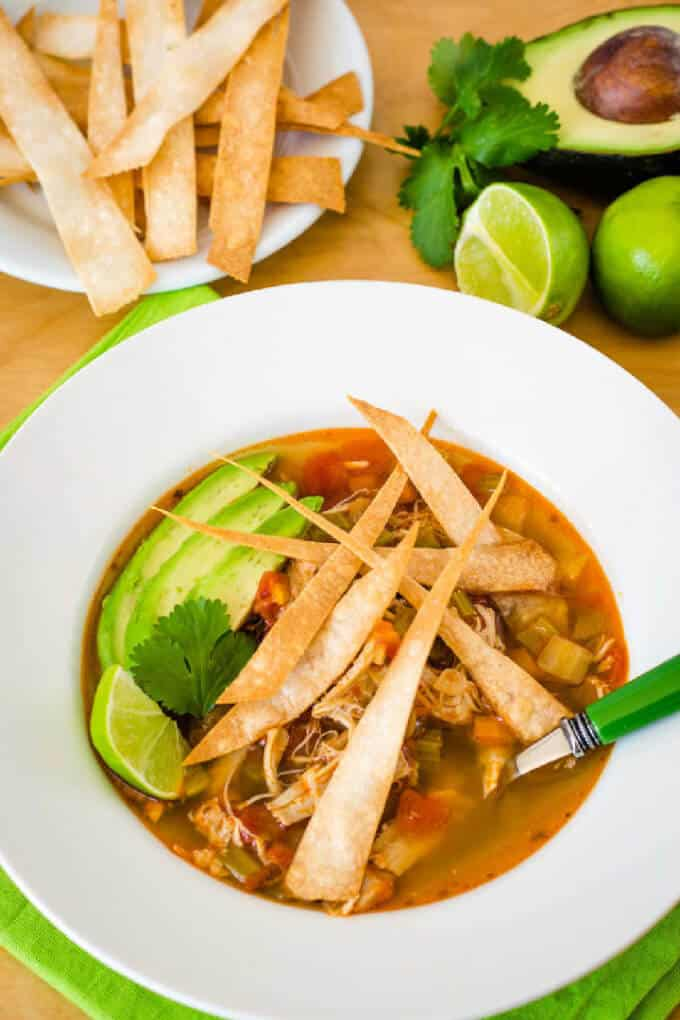 A bowl of Instant Pot chicken tortilla soup with avocado, lime and tortilla strips.