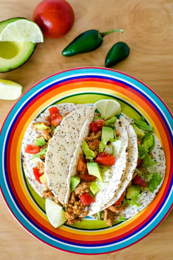 Tacos on plate with avocado, lime, tomato, jalepeno