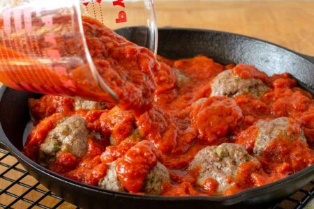 Pouring sauce over par-cooked meatballs