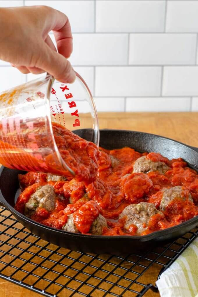 Pouring sauce over meatballs in skillet