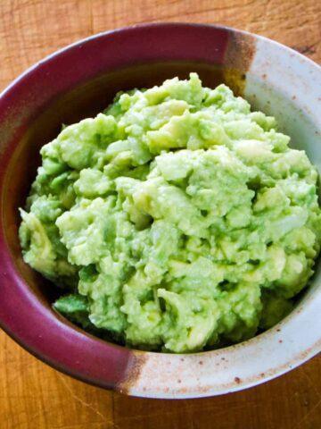 Bowl of guacamole on cutting board